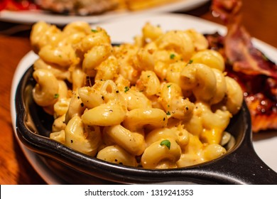Macaroni and cheese also called mac and cheese or mac n cheese served in black small pan. Close up.