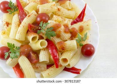 Macaroni with cherry tomatoes, parsley and red pepper served with a tomato sauce close-up