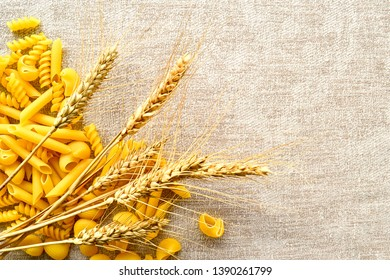 macaroni of different shapes of coarse flour and wheat ears on a beige background with a copy  space- Kuva