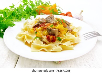Macaroni Farfalle with turkey meat, tomato, yellow sweet pepper with sauce in a plate on the background of a light wooden board