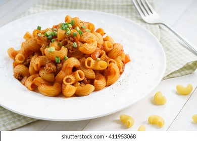 macaroni pasta in tomato sauce with chop meat decorated with scallion on a wooden table