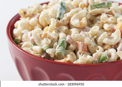 Macaroni salad with cheese and vegetables in a bright red bowl