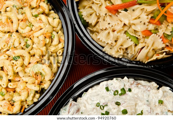 Macaroni salad, pasta salad and potato salad in containers ready to be served.