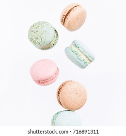 Macarons cake, top view flat lay, fly falling sweet macaroon on white isolated, pastel food background