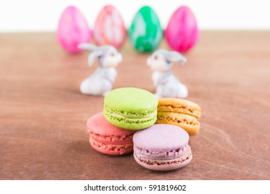Macarons with ceramic bunnies and Easter eggs background