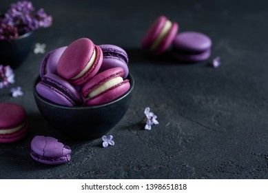 Macarons close up in a black bowl. Pink and purple macaroons with lilac flowers on a dark background