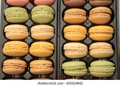 Macarons in different colors and flavors in a plastic tray