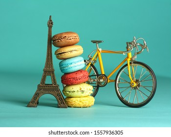 Macarons of different flavors reloaded on the Eiffel tower and a bicycle on a turquoise backgroun