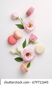 Macarons and flowers on a white background. Colorful french dessert with fresh flowers. Top view