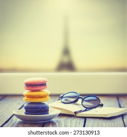 Macarons and little notebook with glasses on wooden table and Eiffel tower background