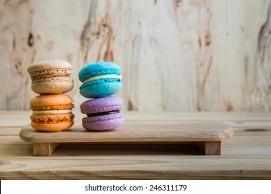 macarons on table over wooden background.