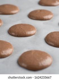 Macarons shells piping on parchment befor baking. Raw macaron dough, macaronage, macarons batter. Process of cooking.