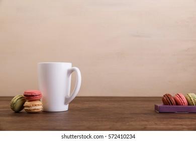 Macaroon cakes. Mockup white tea or coffee cup. Almond sweet cookies. Wooden rustic board.
