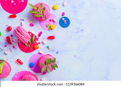 Macaroon cookies on a colorful background with confetti. Vibrant party concept with copy space. Pink and purple palette flat lay.