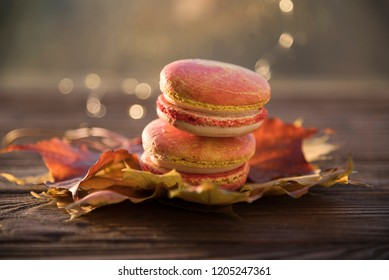 macaroons autumn leaves and bokeh on a dark wooden background.