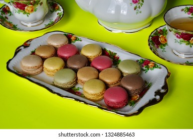 Macaroons in a beautiful plate with tea cups in a saucer in a yellow background