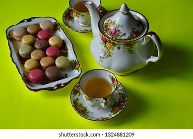 Macaroons in a beautiful plate with teapot and teacups with saucer on the side