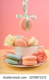 Macaroons cake are placed in a cup with buds of a carnation and roses and one is suspended from above on a gift ribbon with a bow. Copy space. Bakery, cooking, gifts, conceptual and advertising.
