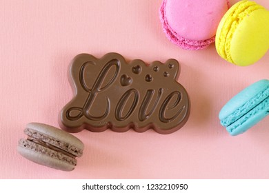 macaroons and chocolate love on a pink background