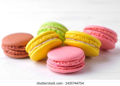 macaroons. delicious colored french macaroni cakes on a white wooden table.