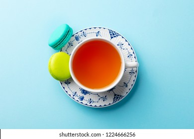 Macaroons dessert and cup of tea on blue background. Top view. Copy space.