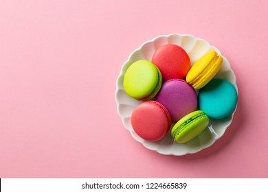 Macaroons dessert on a white plate. Pink pastel background. Top view. Copy space.