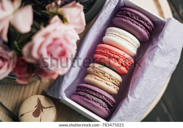 macaroons of different colors with roses