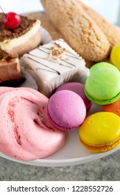 Macaroons, meringues and other sweets on a plate closeup