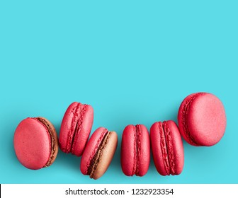 Macaroons on colored background, a lot of colorful french cookies macarons with copy space. Beige, brown french cookies macarons on red background. Gift for Valentine's Day
