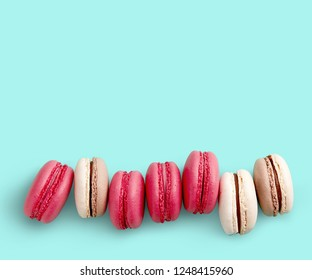 Macaroons on colored background, a lot of colorful french cookies macarons with copy space. Beige, brown and pink french cookies macarons on cyan background. Gift for Valentine's Day