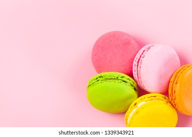 Macaroons on pink background from above, colorful almond cookies, pastel colors