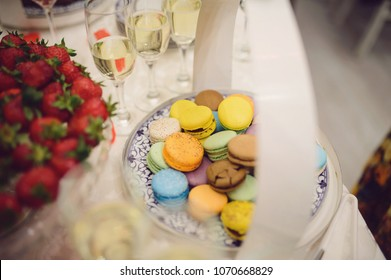 macaroons on table with strawberry and glasses of champagne