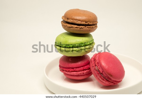 Macaroons on the white ceramic plate and background.