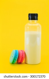 Macaroons on wooden tray  and a bottle of milk on yellow background