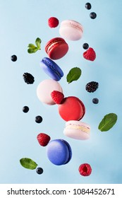 Macaroons, raspberries, blackberries and blueberries flying over blue background