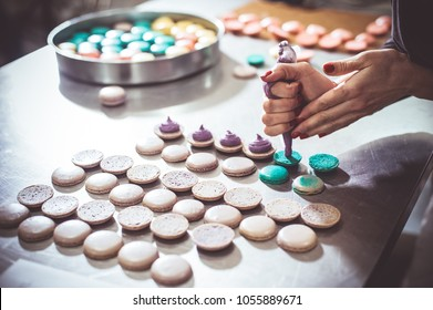 macaroons shells in a tray fresh from oven. Process of making macaron macaroon , french dessert, squeezing the dough form cooking bag. Food industry, mass or volume production.