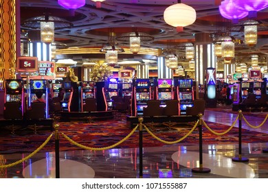 MACAU, CHINA- 06 APR, 2018: Arcade machines and gamblers inside casino in Macau