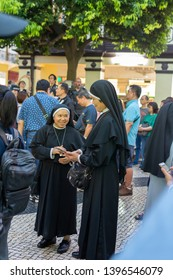 Macau, China, 13th May 2019. 2 Nouns talking while waiting for the Procession of Our Lady of Fátima to start
