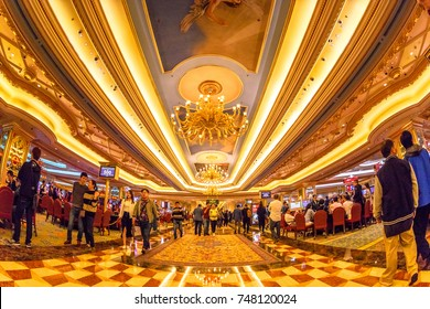 Macau, China - December 8, 2016: Luxury gamble corridor with game tables and machines of Venetian Hotel and Casino. Elegant people visiting and gambling from all the world.