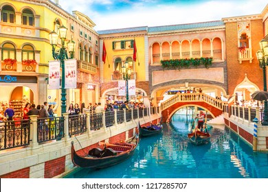 Macau, China - December 9, 2016: Canals with Venetian bridge of the Venetian style Casino. Inside luxury shopping mall in the Venetian Hotel in Cotai Strip.