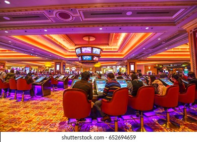 Macau, China - December 9, 2016: people visit The Venetian Casino hall with game machines. The Venetian is the largest casino in the world and the largest single structure hotel building in Asia.
