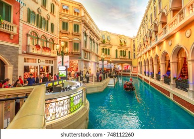 Macau, China - December 9, 2016: gondolier with tourists during a ride in an authentic gondola down Grand Canals at the Venetian Casino. Inside luxury shopping mall in the Venetian Hotel, Cotai Strip.