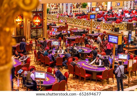 Macau, China - December 9, 2016: aerial view of blackjack tables and gamblers inside The Venetian Casino in Macau. Macau is the capital of casinos and Asian gambling and, now, in the world.