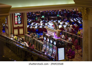 Macau, China - JUL 10 : People are playing slot machines in Venetian Hotel, Macao on July 10, 2015.The Venetian Hotel is the famous shopping mall, luxury hotel and the largest casino in the world.
