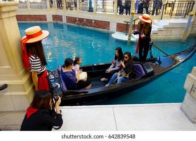MACAU, CHINA- MAY 11, 2017: An unidentified people having a trip in a venetian gondola inside of a beautiful luxury hotel the Venetian Resort Hotel and Casino