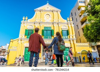 MACAU, CHINA - NOV 22, 2017: Lovely Asian couple standing in front of St. Dominic's Church. It is the Roman Catholic Diocese of Macau.