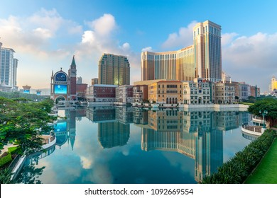 MACAU, CHINA - NOVEMBER 19 : Venetian hotel and casino with surrounding buildings in Macau reflection in the water under cloudy blue sky, China, on November 19, 2015.
