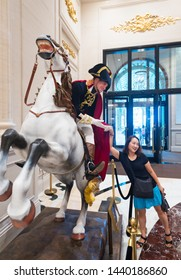 MACAU, CHINA - SEPTEMBER 15, 2017: An actor dressed as Napoleon poses with a young visitor at the Parisian hotel hall. Macau's gaming revenue has been the world's largest since 2006.