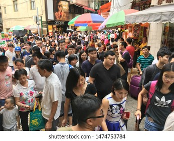 MACAU, CHINA - SEPTEMBER 16, 2017: Lots of people crowd the center of the city. With a population of 667,400 and an area of 32.9 km2 (12.7 sq mi), it is the most densely populated region in the world.