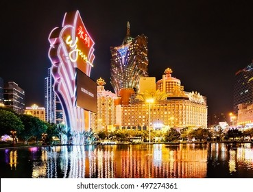 Macau - January 24, 2016: Grand Lisboa Hotel night lights are reflected from the surface of the Wynn Palace's performance lake